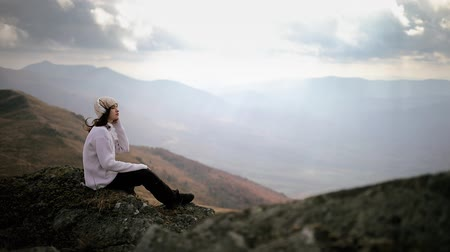 Young stylish woman in headphones sits on a rock on top of a mountain and listens to music. The girl enjoys beautiful mountain scenery and freedom
