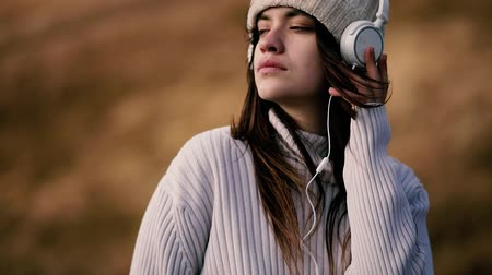 Close up portrait of woman in headphones sits on a rock on top of a mountain and listens to music. Breeze is playing with girls hair