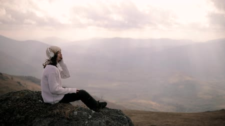 Stylish girl in headphones sits on a rock on top of a mountain and listens to music