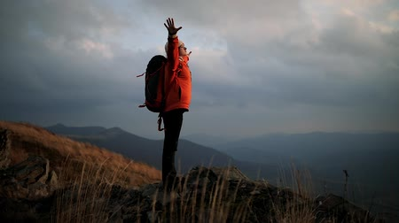 Young beautiful woman walks up to the edge of a cliff at the top of a mountain and raises her hands up to meet the sunset. Woman enjoys windy weather and incredible mountain landscape Stock Footage