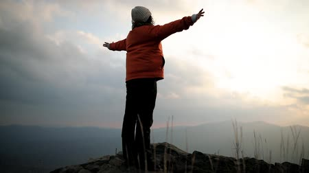 The camera revolves around a young beautiful woman standing on the edge of a cliff at the top of a mountain and raises her hands up to meet the sun. Happy and drunk on life, youth and happiness