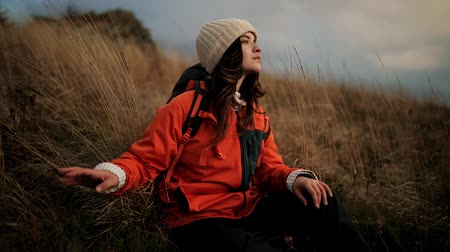 Cute hiker girl with backpack sits in tall grass on top of mountain and enjoys incredible scenery. Young woman feels harmony and unity with nature