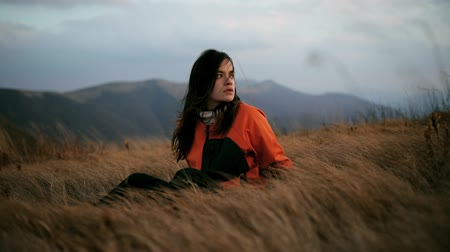 Beautiful dark-haired hiker girl with a backpack sits on top of a mountain and looks at the scenery around. Young woman feels harmony and unity with nature Stock Footage