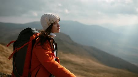 Charming dark-haired young woman with a backpack sits on a rock and enjoys an incredible mountain landscape. Woman enjoys windy weather. The girls long dark hair flutters in the wind