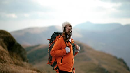 A young woman is standing on top of a mountain and watching the sunset. Lovely girl enjoys freedom in the mountains, happy and drunk on life, youth and happiness Stock Footage