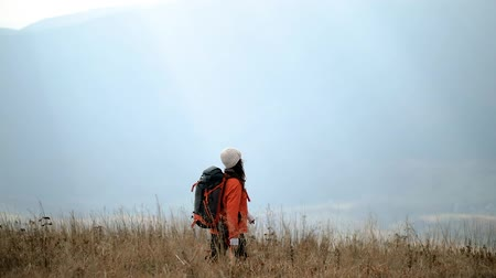 Hiker girl with backpack walks through tall grass on top of mountain. Romantic woman enjoys freedom in the mountains, happy and drunk on life, youth and happiness