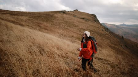 winnings : Young beautiful hiker woman with backpack goes to the top of the mountain. The girl enjoys the mountain scenery and windy weather. Romantic girl enjoys freedom in the mountains Stock Footage