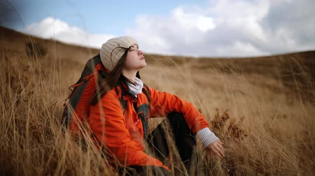Cute hiker girl sits in tall grass on top of mountain. Young woman enjoys the gusts of wind that flutter her long dark hair. Young woman feels harmony and unity with nature