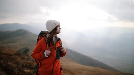 Young beautiful woman tourist stands on top of mountain and enjoys incredible view. Hair blowing in the wind. Girl admiring mountain landscape. Romantic girl enjoys freedom in the mountains