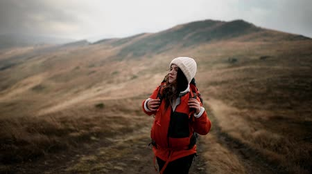Young beautiful hiker woman with backpack goes to the top of the mountain. The girl enjoys the misty mountain scenery and windy weather. Romantic girl enjoys freedom in the mountains