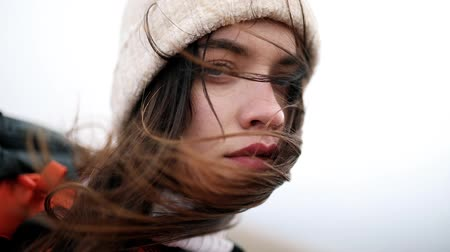Close up portrait of woman standing on the wind. Breeze is playing with girls hair. Stormy weather, autumn, winter, spring
