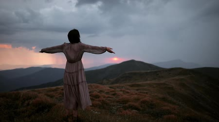 Camera moves around beautiful woman in light long dress lifting her hands up against sunset on mountain top. Girl in a long dress that flutters in the wind. Sunset before rain and thunderstorm Stock Footage