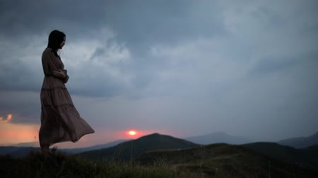Static still with a girl in a long dress fluttering in the wind at the top of the mountain. Dramatic sunset before rain and thunderstorm Stock Footage