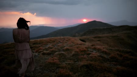 A young woman in a long dress walks on top of a mountain toward sunset. Dramatic red sunset before rain and thunderstorm. Girl in a long dress that flutters in the wind Stock Footage