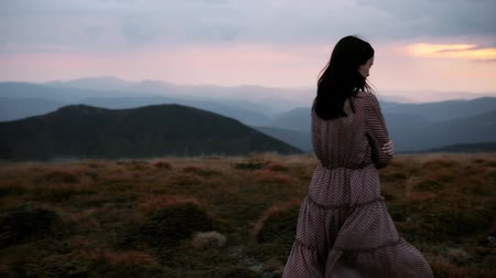 Pensive beautiful young woman in long dress walks on top of mountain. Dramatic mountain landscape with red sunset before rain and thunderstorm