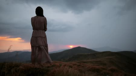 Young mysterious girl in a long dress stands on top of a mountain and enjoys the view. Dramatic mountain landscape with red sunset before rain and thunderstorm