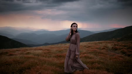 Pretty brunette girl in a long dress straightens her hair while walking on top of a mountain. Dramatic mountain landscape with red sunset before rain and thunderstorm Stock Footage