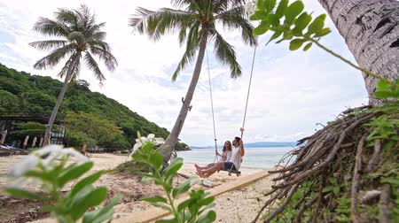 turk : A young couple swinging on a swing on a tropical beach. Couple in love on a beach swing by the sea in southeast Asia. Stock Footage