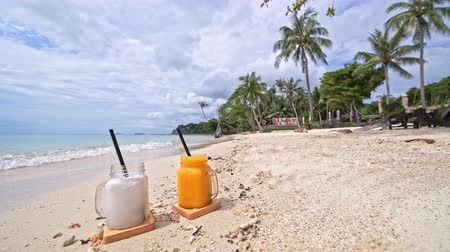 manga : Fruit smoothies stand on the sand on the beach with palm trees. Healthy food.