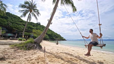 turk : Young happy man swinging on a swing in the palm trees on the ocean. Beautiful European on a swing on the coast of Southeast Asia