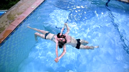 brasileiro : A young couple swims in the pool.