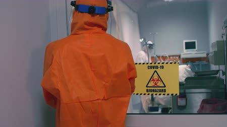megelőzés : Doctor in an Orange Protective Suit Enters Isolation Room with Coronavirus Patients