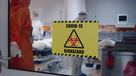 óculos de proteção : Doctor in an Orange Protective Suit Enters Isolation Room with Coronavirus Patients