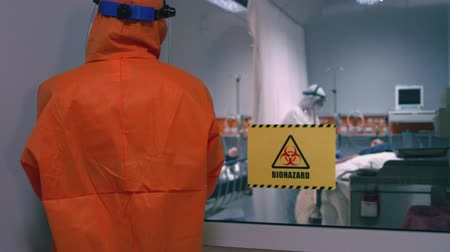 стручок : Doctor in an Orange Protective Suit Enters Isolation Room with a Sign Reading Biohazard n the Door Стоковые видеозаписи