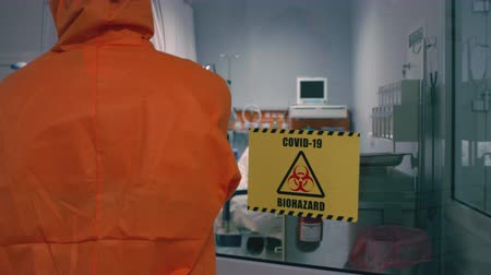 infectious : Doctor in an Orange Protective Suit Enters Isolation Room with Coronavirus Patients