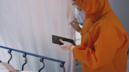 protective suit : Doctor in an Orange Protective Suit Enters Isolation Room with Coronavirus Patients - SLOW MOTION Handheld Shot Stock Footage