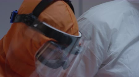zavřít : Nurse in a Protective Suit Measuring Coronavirus Patients Temperature and Consulting with Leading Doctor - Close Up Tilting Shot