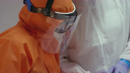 infectious : Nurse in a Protective Suit Measuring Coronavirus Patients Temperature and Consulting with Leading Doctor - Close Up Tilting Shot