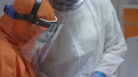 megelőzés : Nurse in a Protective Suit Measuring Coronavirus Patients Temperature and Consulting with Leading Doctor - Close Up Tilting Shot