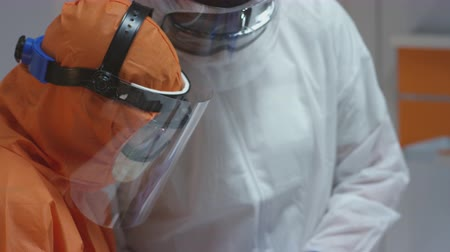 respiratory : Nurse in a Protective Suit Measuring Coronavirus Patients Temperature and Consulting with Leading Doctor - Close Up Tilting Shot