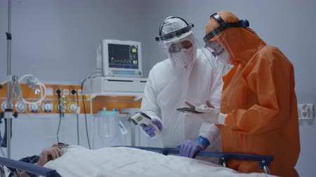 respiratory infection : Nurse Measuring Coronavirus Patients Temperature and Consulting with Leading Doctor - Wide Dolly Shot