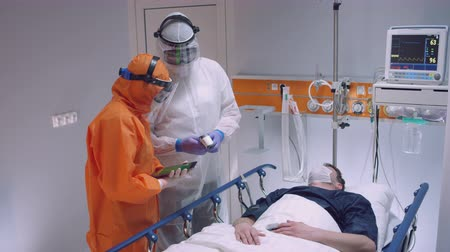 infectious : Nurse in a Protective Suit Measuring Coronavirus Patients Temperature and Consulting with Leading Doctor - Wide Shot Stock Footage