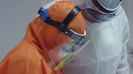 pacjent : Nurse in a Protective Suit Measuring Coronavirus Patients Temperature and Consulting with Leading Doctor - Close Up Tilting Shot