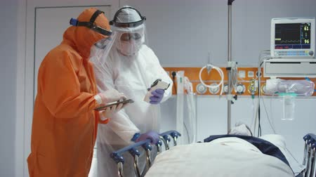 pacjent : Nurse in a Protective Suit Measuring Coronavirus Patients Temperature and Consulting with Leading Doctor - Wide Dolly Shot Wideo