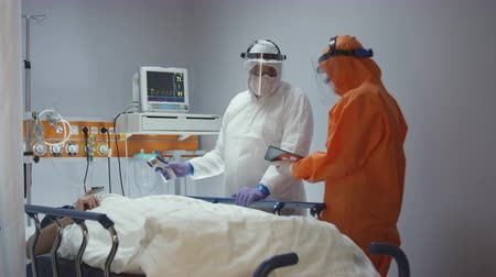 Nurse Measuring Coronavirus Patients Temperature and Consulting with Leading Doctor - Wide Dolly Shot