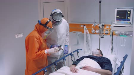 pacjent : Nurse in a Protective Suit Measuring Coronavirus Patients Temperature and Consulting with Leading Doctor - Wide Shot Wideo