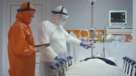 respiratory infection : Nurse in a Protective Suit Measuring Coronavirus Patients Temperature and Consulting with Leading Doctor - Wide Dolly Shot Stock Footage