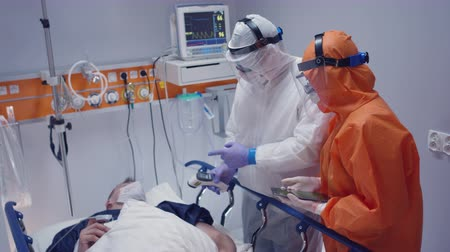 tiro : Nurse in a Protective Suit Measuring Coronavirus Patients Temperature and Consulting with Leading Doctor - Wide Shot Stock Footage