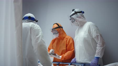 protective suit : Nurse in a Protective Suit Measuring Coronavirus Patients Temperature and Consulting with Leading Doctor - Wide Dolly Shot Stock Footage