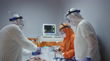 dünya çapında : Nurse in a Protective Suit Measuring Coronavirus Patients Temperature and Consulting with Leading Doctor - Wide Dolly Shot Stok Video
