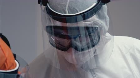 Doctors in Protective Suits Consult Coronavirus Patients Status - Close Up Panning Shot Stock mozgókép