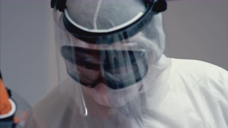 protective suit : Doctors in Protective Suits Consult Coronavirus Patients Status - Close Up Panning Shot Stock Footage
