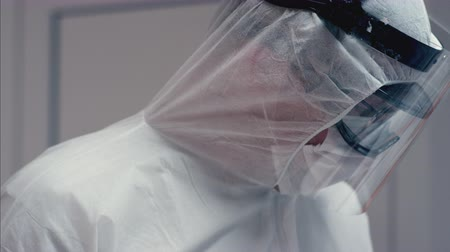 prevenire : Doctors in Protective Suits Consult Coronavirus Patients Status - Close Up Panning Shot in Slow Motion