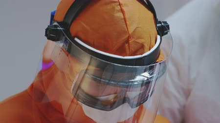 発熱 : Doctors in Protective Suits Consult Coronavirus Patients Status - Close Up Shot in Slow Motion