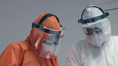 prevenire : Doctors in Protective Suits Consult Coronavirus Patients Status - Close Up Dolly Shot Filmati Stock