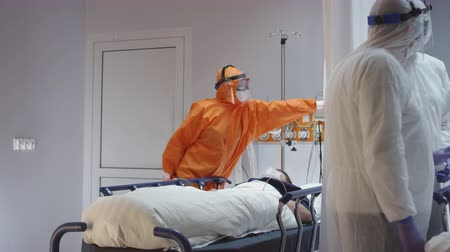 pacjent : Doctor in Orange Protective Suit Turning On Coronavirus Pateints Heart Monitor - Wide Dolly Shot in Slow Motion